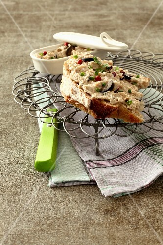 Tuna paté on toast with olives and pink pepper