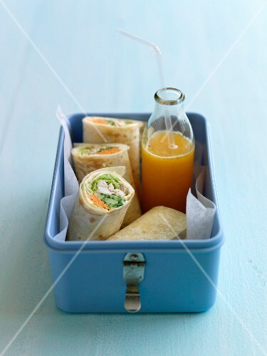 Chicken and vegetable wraps and orange juice in a lunch box