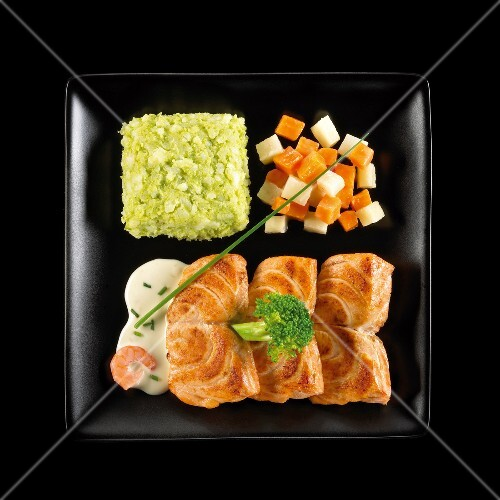 Pan-fried salmon with diced vegetables and green mash on a black background