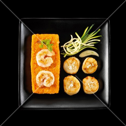 Roasted scallops,carrot mash with king prawns on a black background