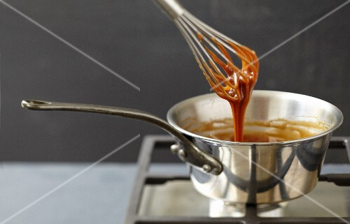Slowly mixing the toffee in the saucepan with a whisk