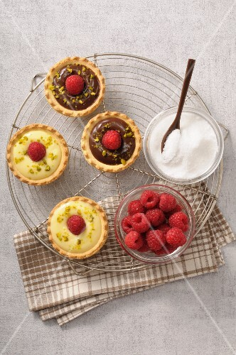 White and dark chocolate tartlets topped with freshed raspberries and crushed pistachios
