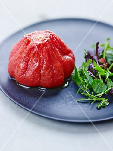 A preserved tomato with oil and coarse sea salt