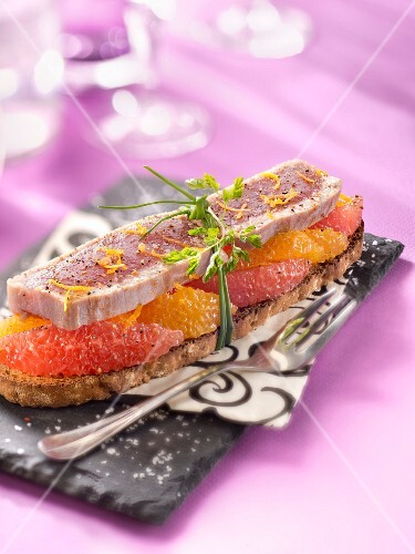 Half-cooked tuna and citrus fruit on toast