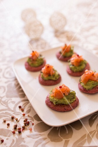 Beetroot blinis garnished with guacamole and smoked salmon