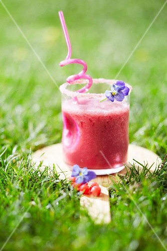 Redcurrant smoothie in the grass outdoors