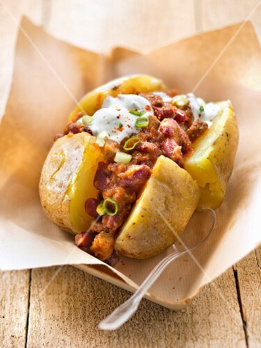 Baked potato garnished with chili con carne