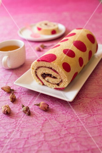 Strawberry jam rolled sponge cake decorated with pink spots