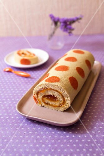 Apricot jam rolled sponge cake decorated with orange spots