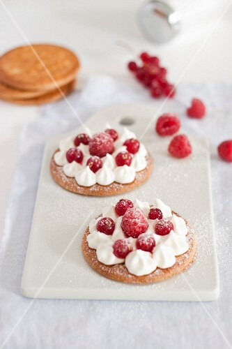 Shortbreads topped with whipped cream and raspberries