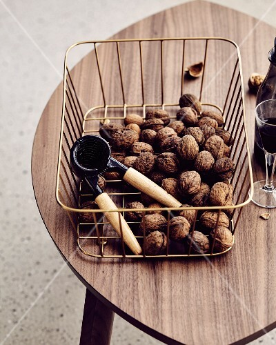 Walnuts and a nutcracker in a metal basket