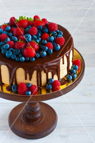 Sponge cake coated in chocolate and topped with summer fruit