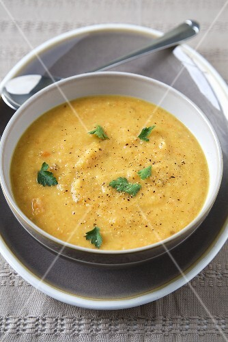 Carrot, Lentil and Coriander Soup in a Bowl; Spoon