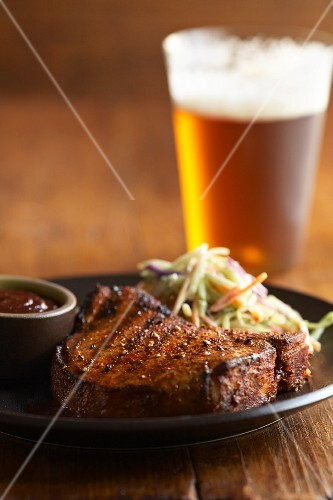 Grilled pork chop with cabbage salad and a glass of beer