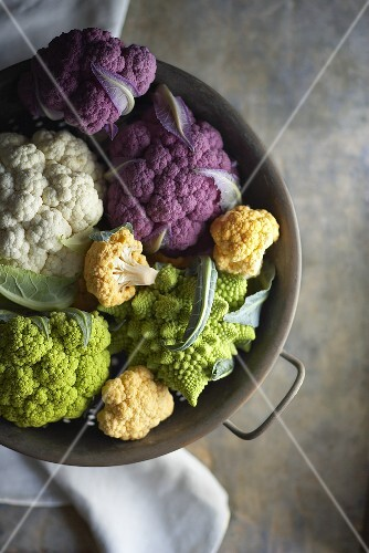 Variety of Fresh Cauliflower in a Metal Colander; From Above