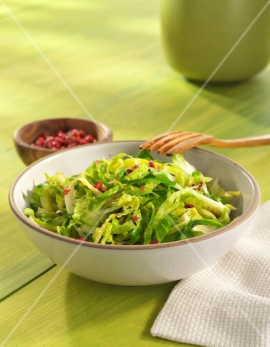 Shredded Brussels Sprouts in a white Bowl with Bacon Bits
