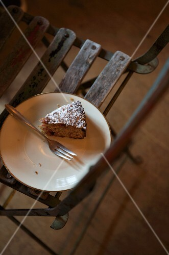 A slice of cake on a plate on a wooden chair