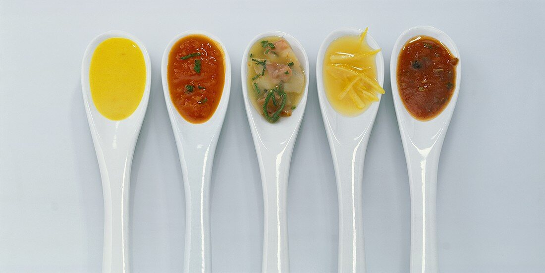 Five different gravies on spoons