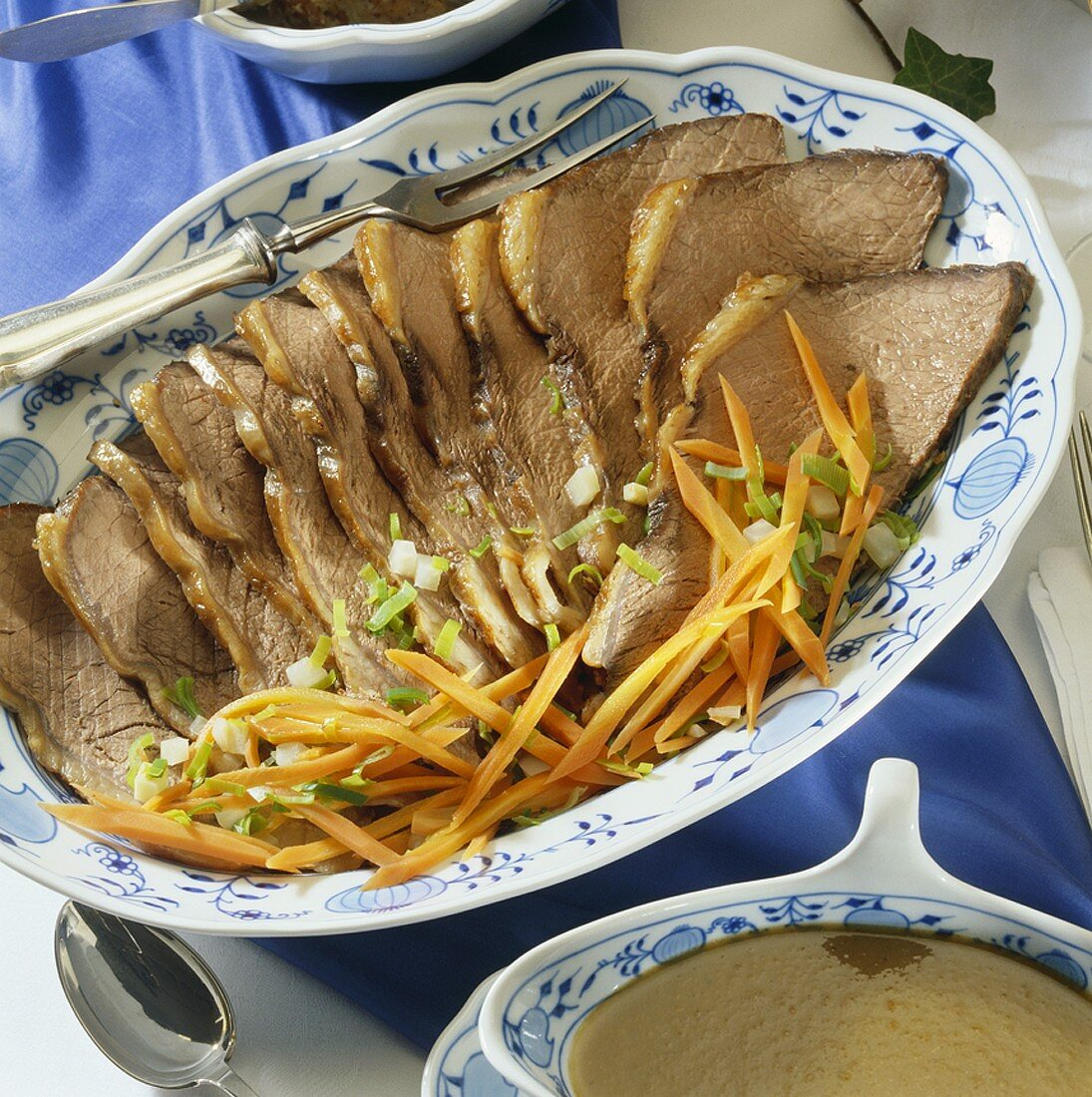 Sliced Sauerbraten (braised, marinated meat) with root vegetables