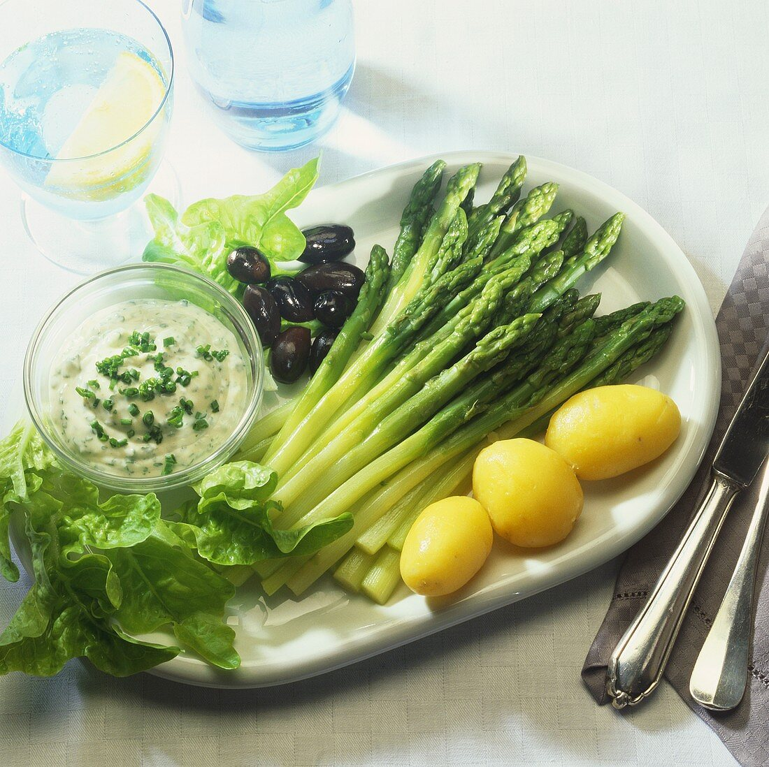 Green asparagus with potatoes, olives and garlic cream