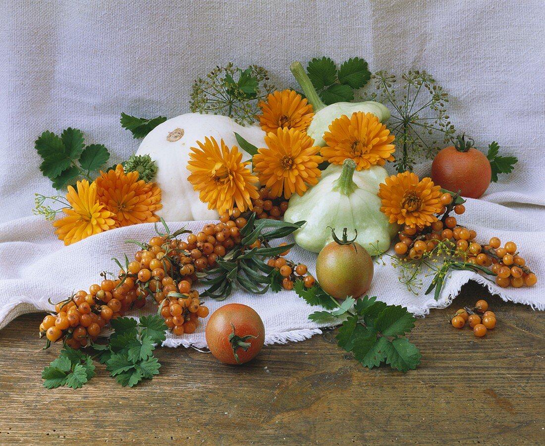 Arrangement of sea buckthorn berries, patty pan squashes & marigolds