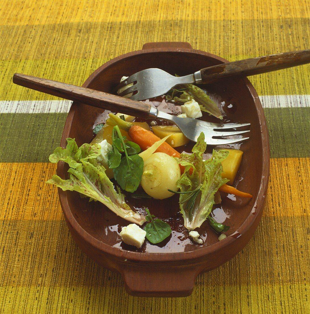 Half-eaten root vegetable salad in wooden bowl