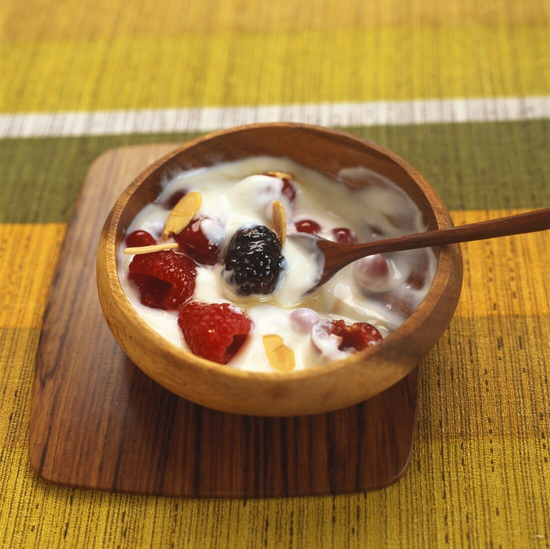 Yoghurt with red berries, honey and almonds in wooden bowl