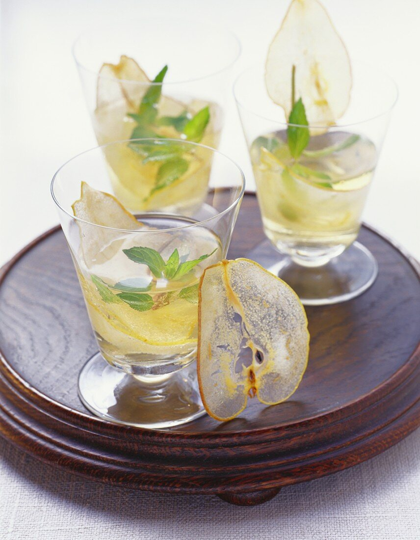 Three glasses of pear cocktail with dried pear slices