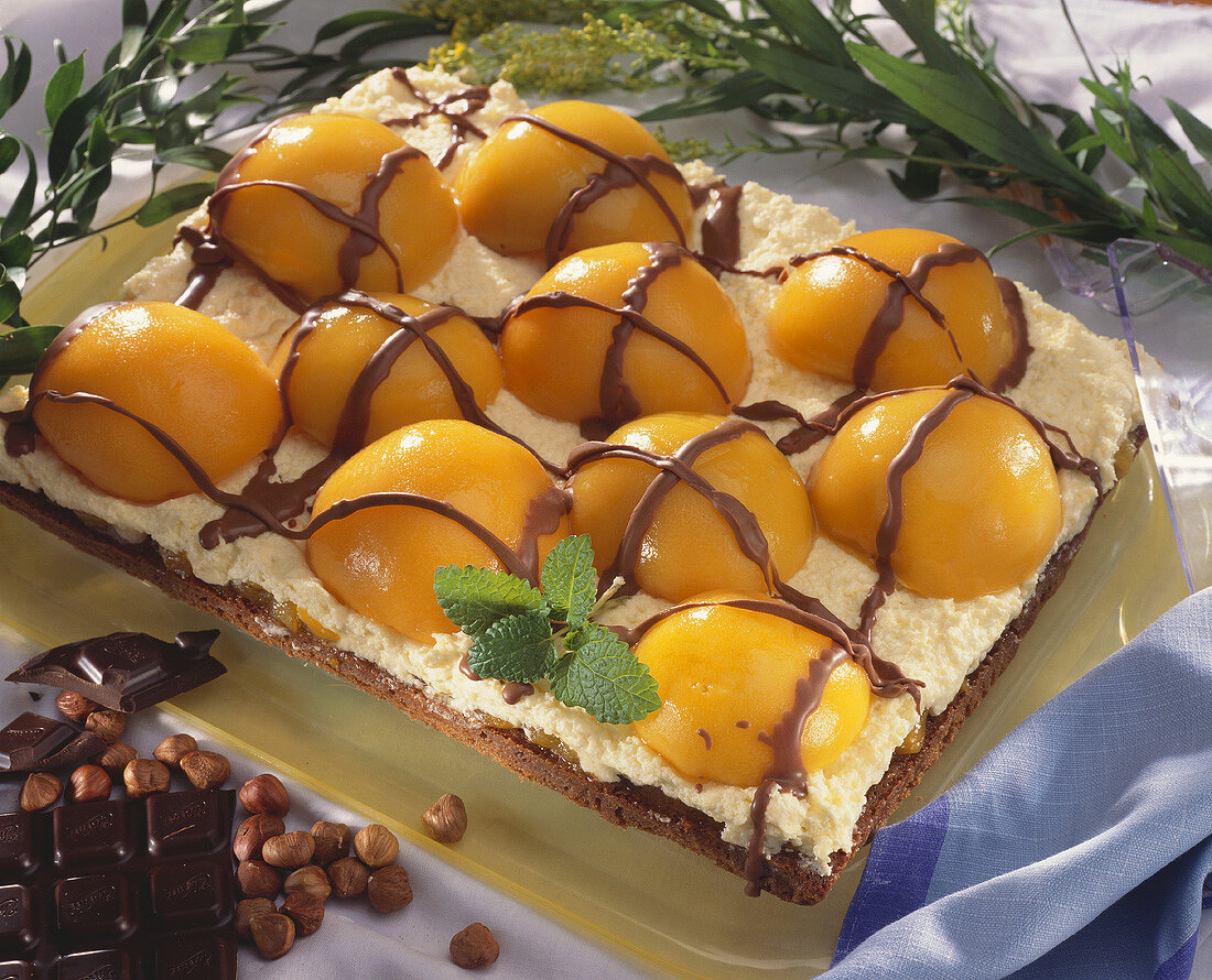 Chocolate nut cake topped with whipped cream and apricots