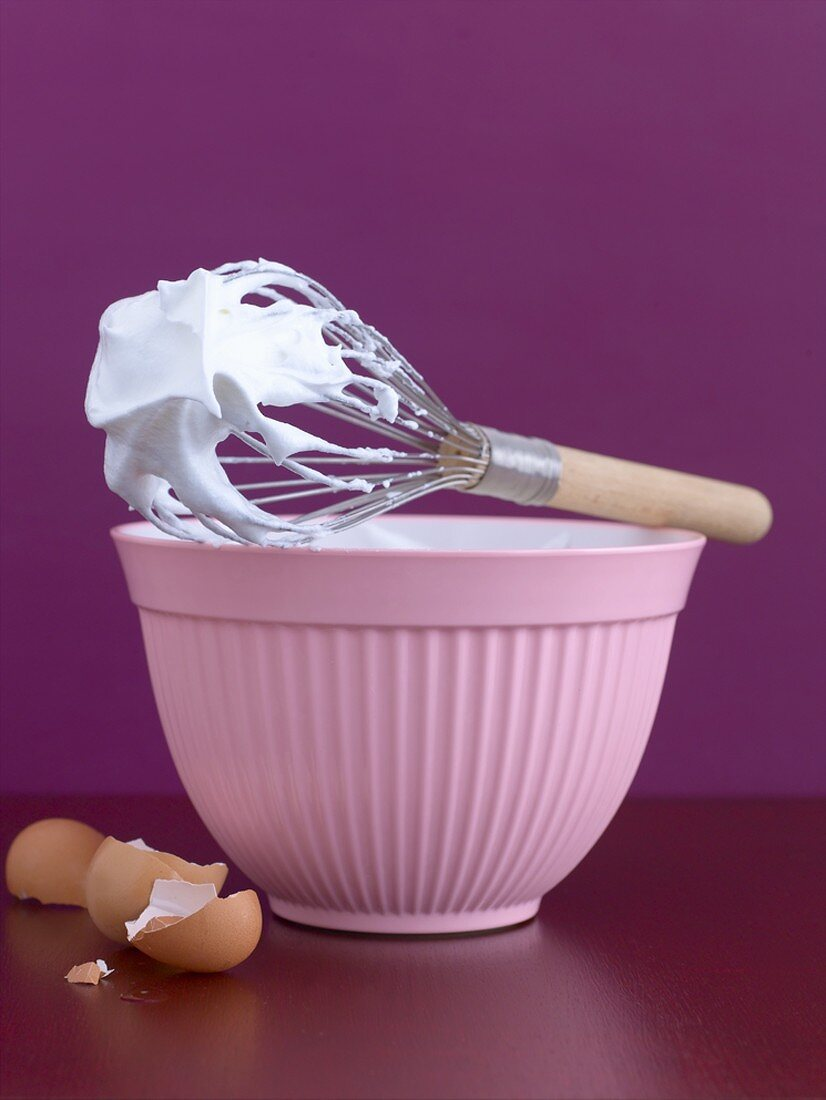 Bowl of beaten egg white with whisk