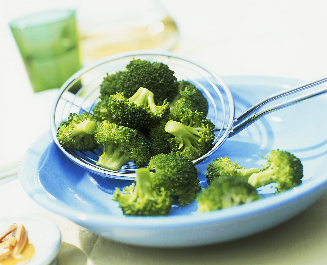 Broccoli florets on straining spoon
