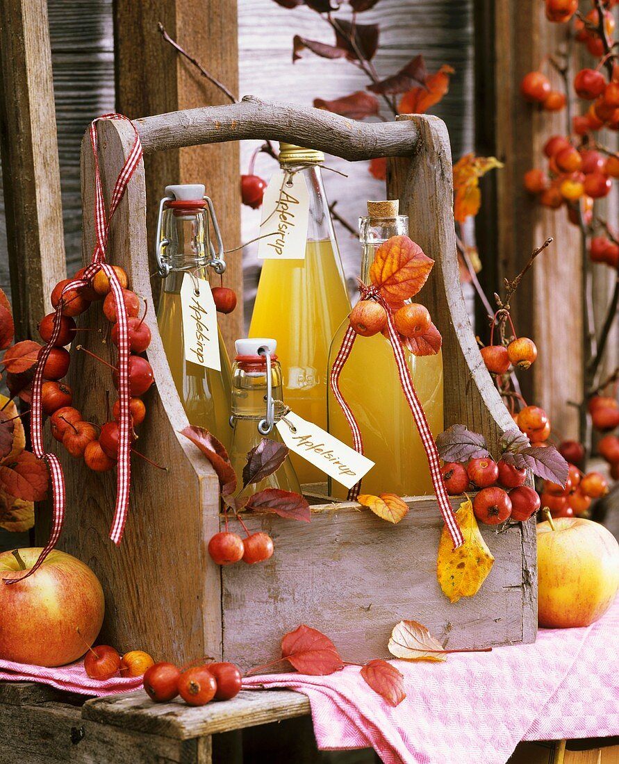 Four bottles of home-made cloudy apple juice in wooden carrier