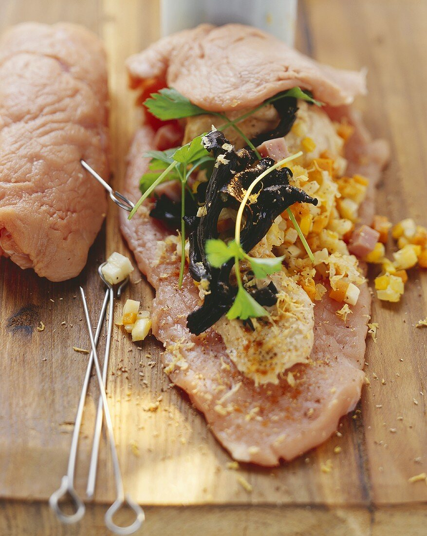 Making veal roulades with ham and vegetable stuffing