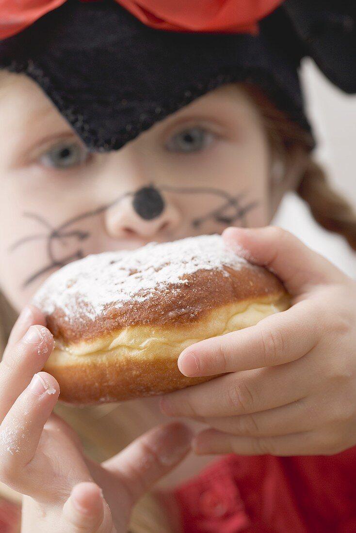 Girl in fancy dress eating a doughnut (Carnival)