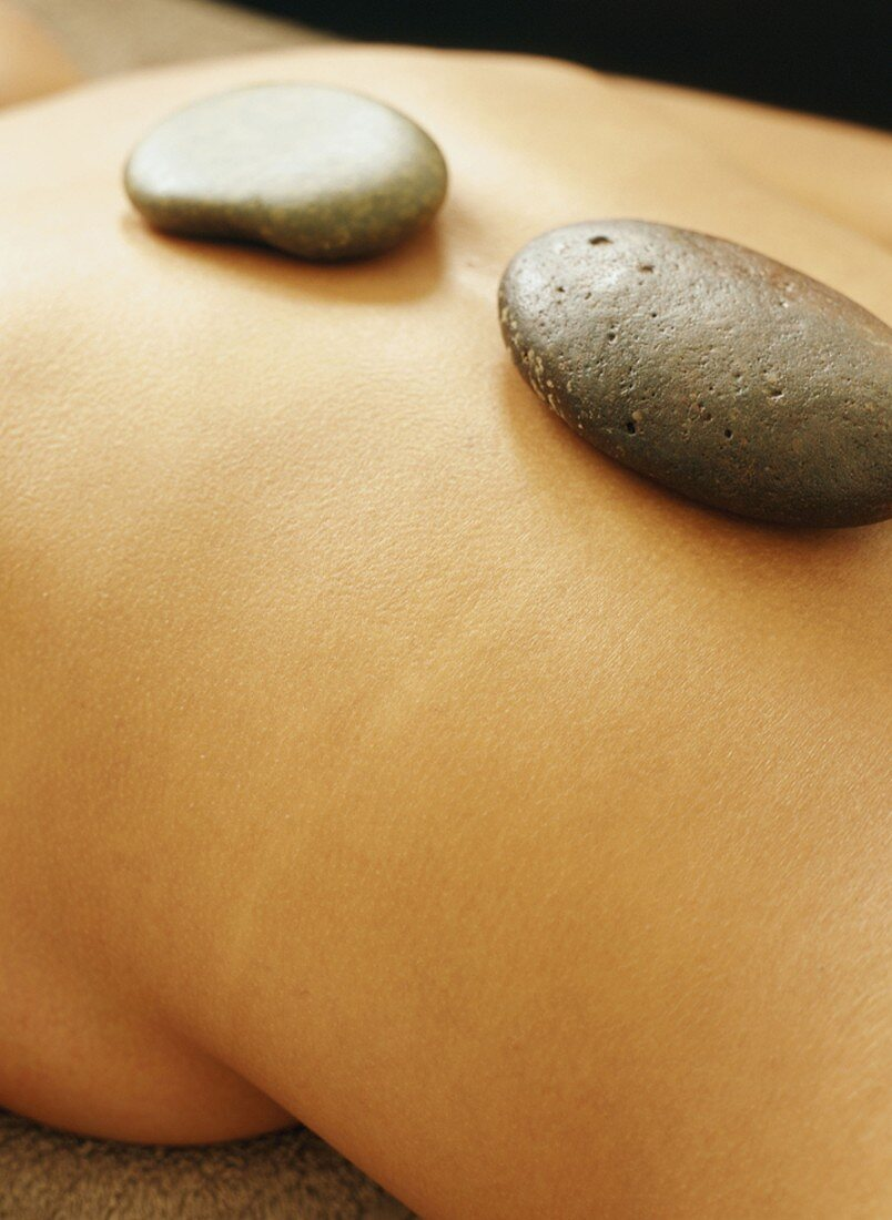 LaStone therapy: warm stones on a woman's back