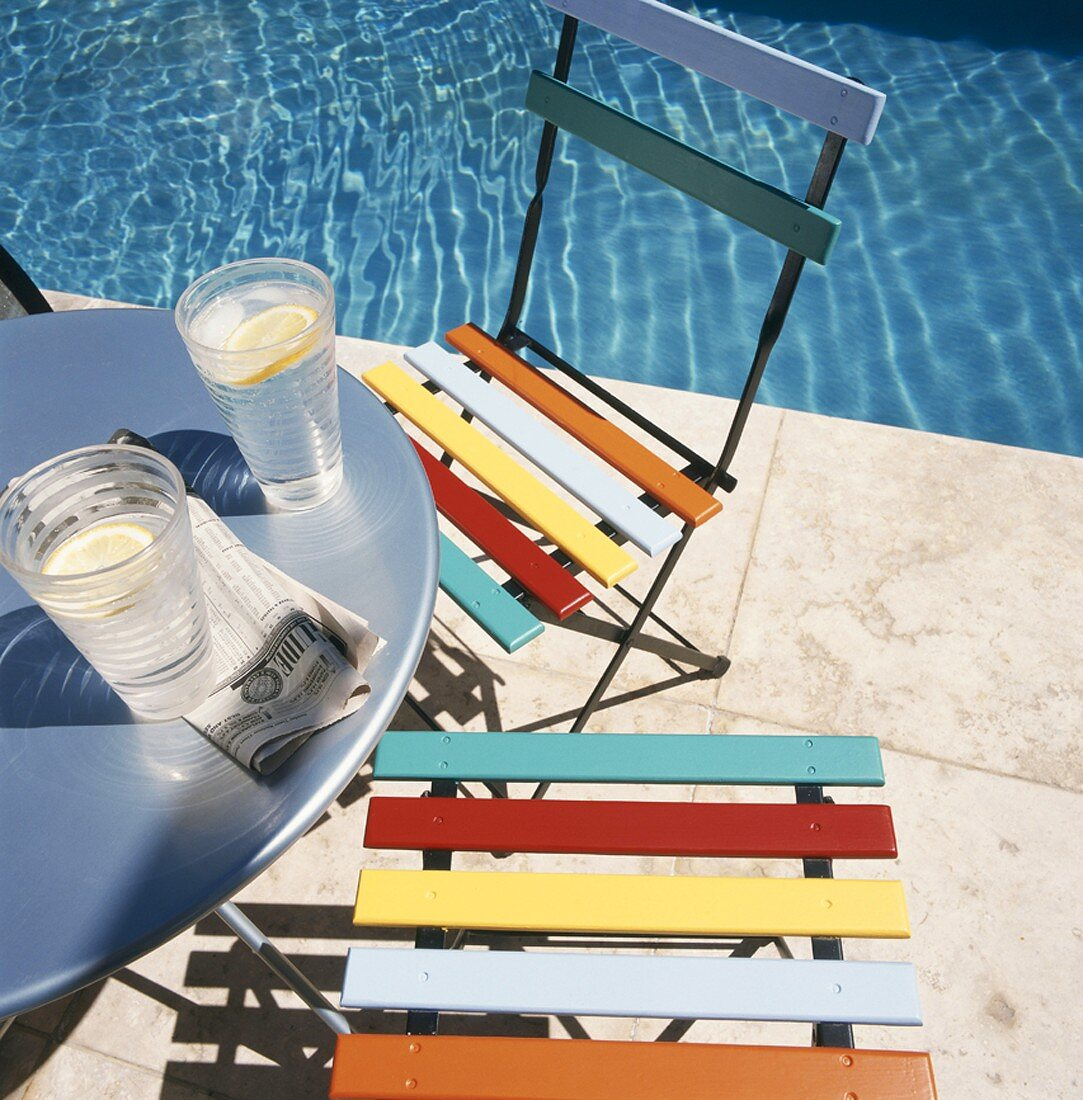 Two glasses on water on table next to pool