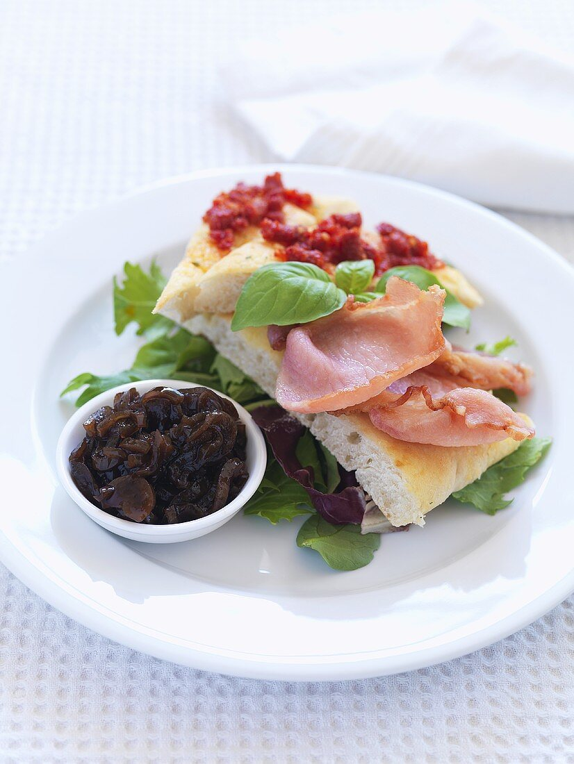 White bread, fried bacon and onion relish on plate