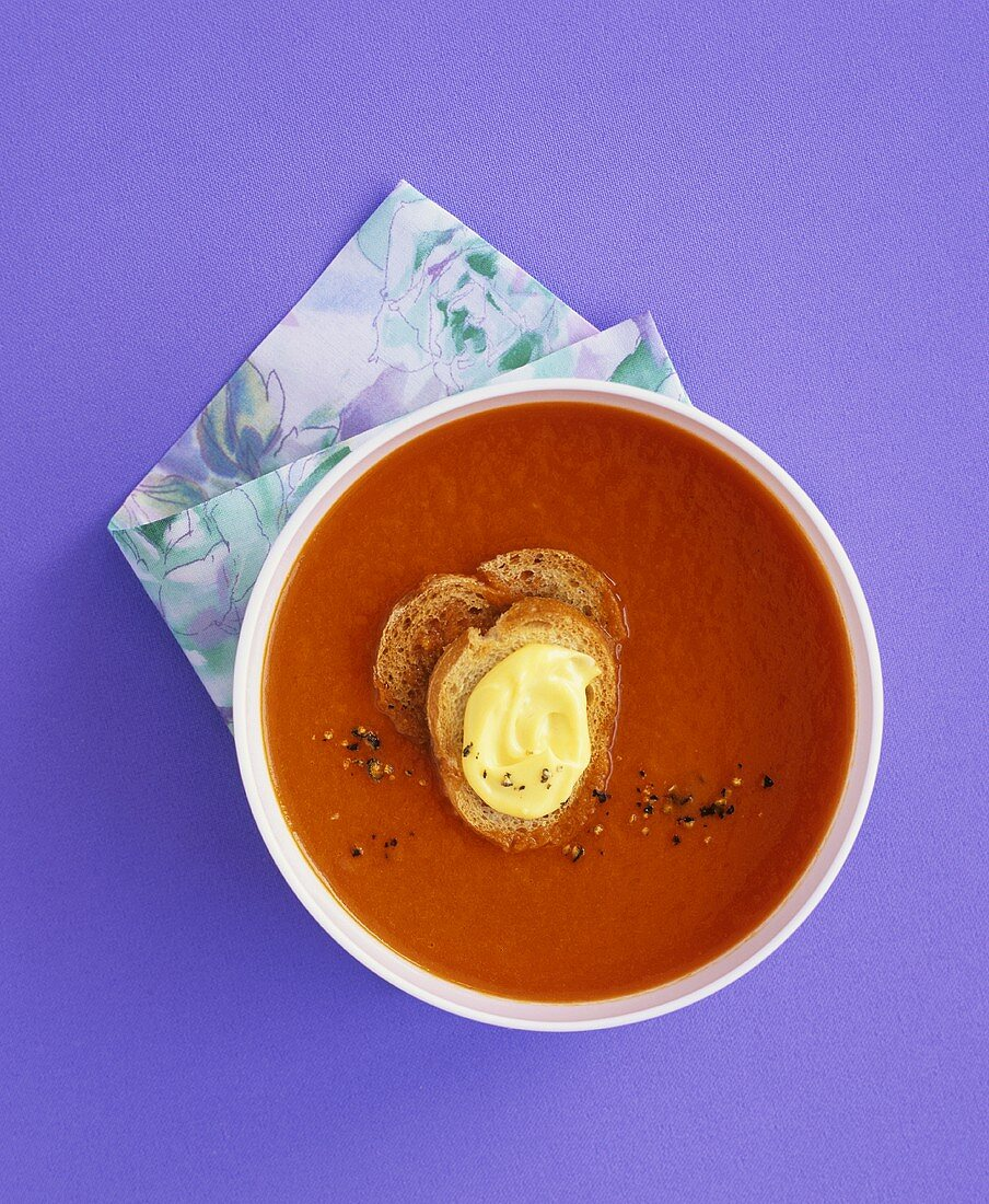 Cold red pepper soup with saffron mayonnaise on crostini