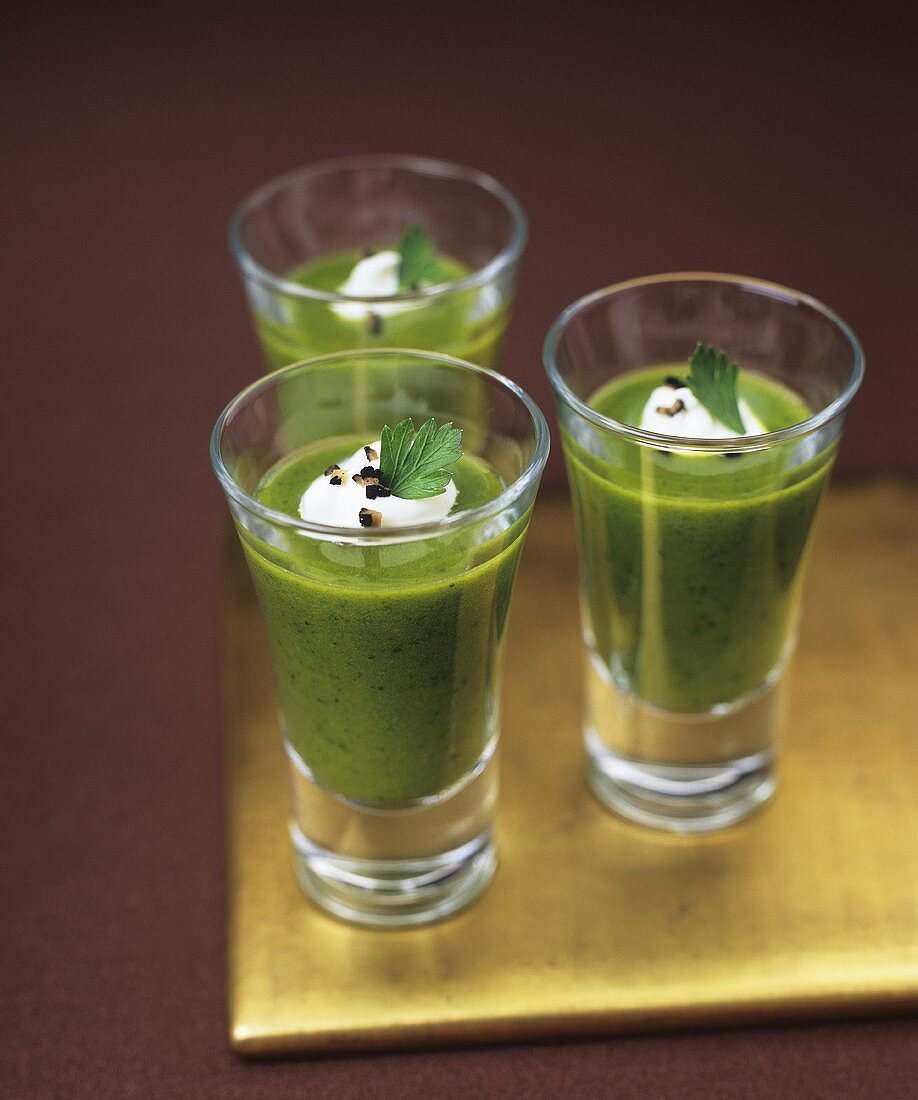 Parsley soup with black truffles in glasses