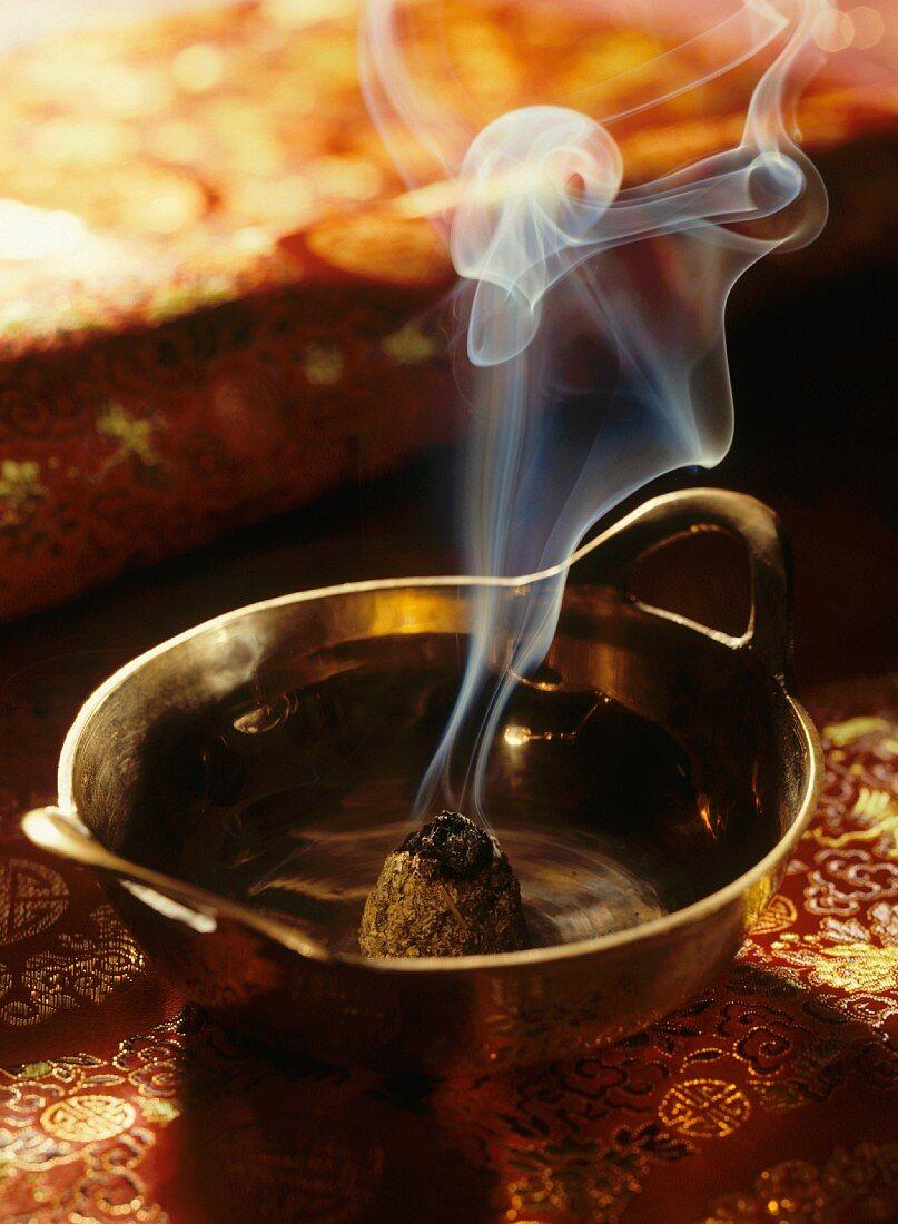 Burning moxa cone in brass dish