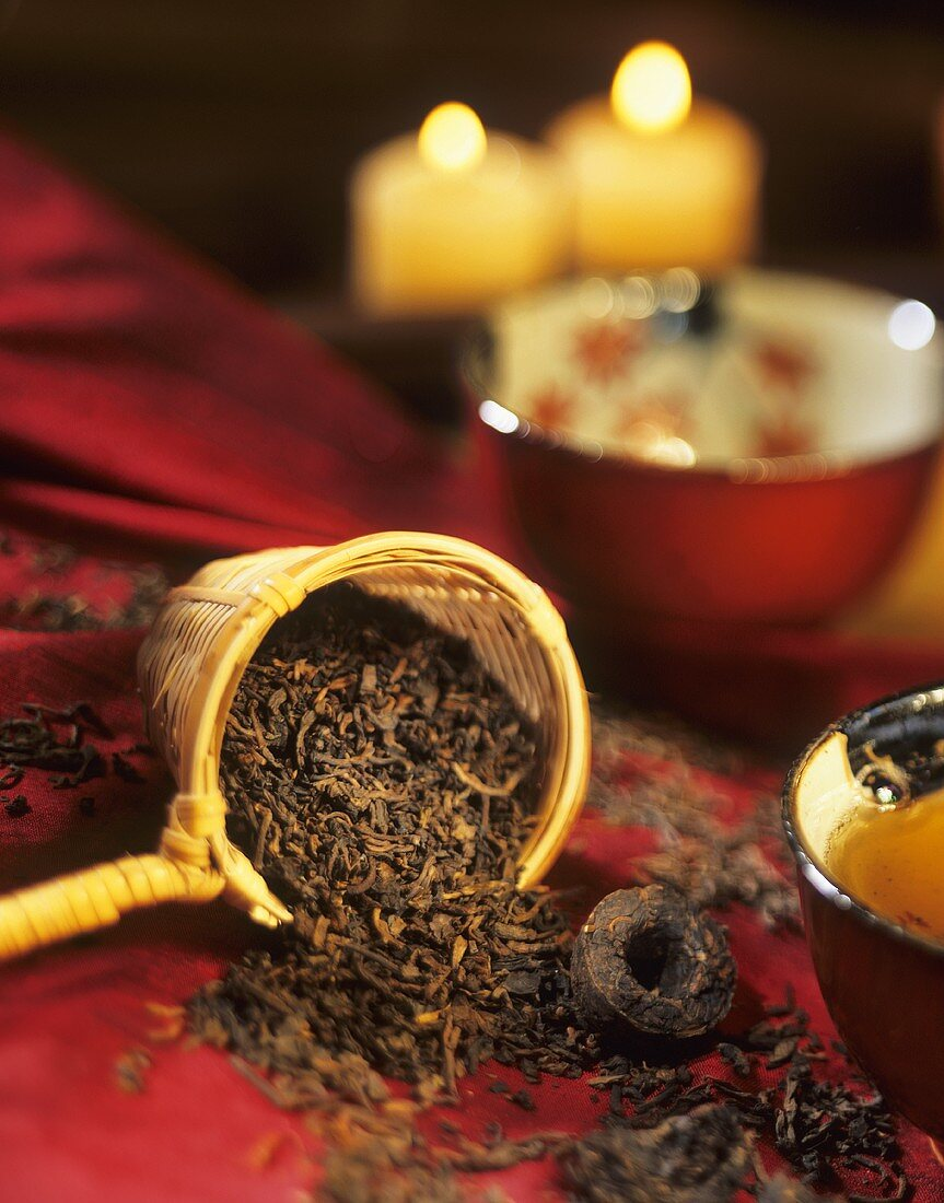 Pu-erh tea in tea bowl, loose tea leaves and pressed tea