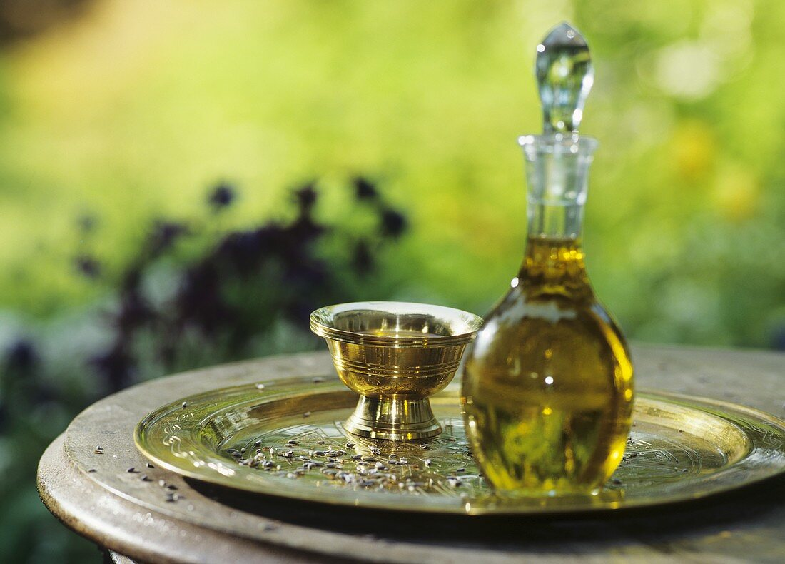 Body oil in glass bottle with stopper and brass dish on tray