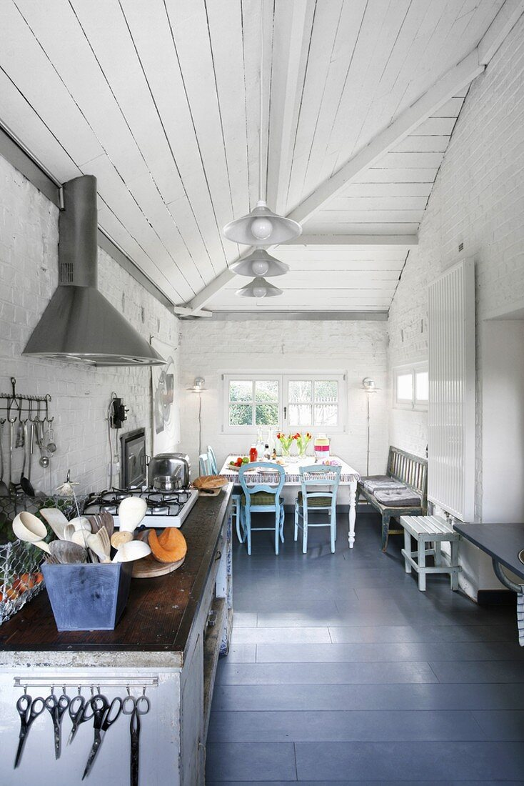 Blick durch eine Küche mit antiker Herdzeile und Vintageessecke