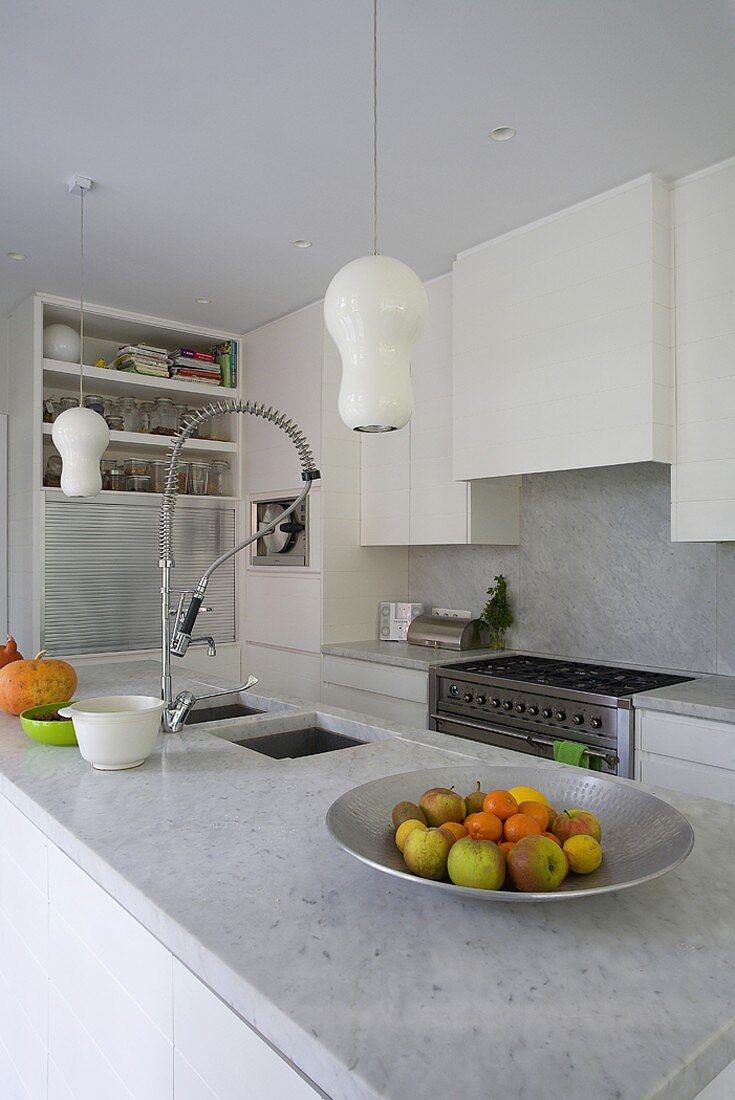 Marmorküchenblock mit Spülbrause einer modernen Einbauküche in Weiss