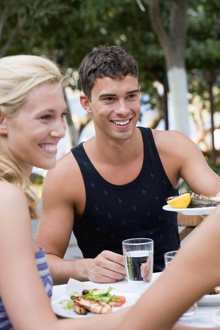 Man and woman at table with Mediterranean fish dishes