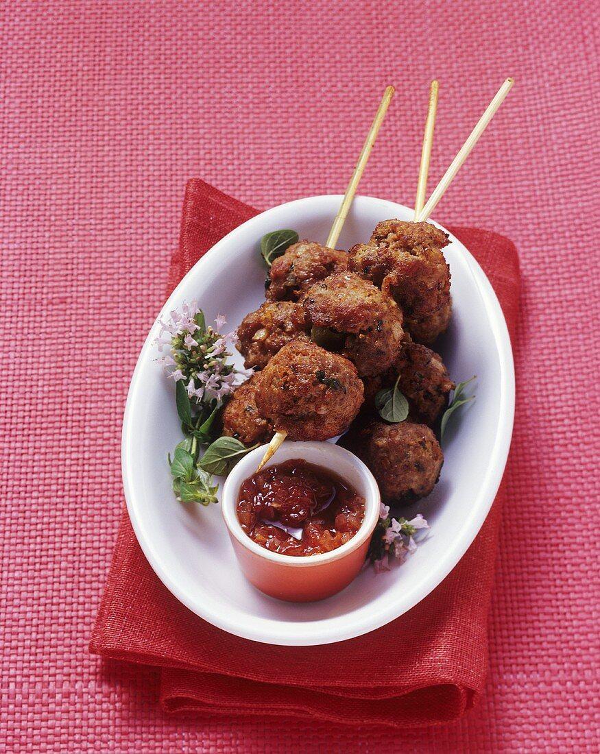 Stuffed meatballs on skewers with tomato chutney