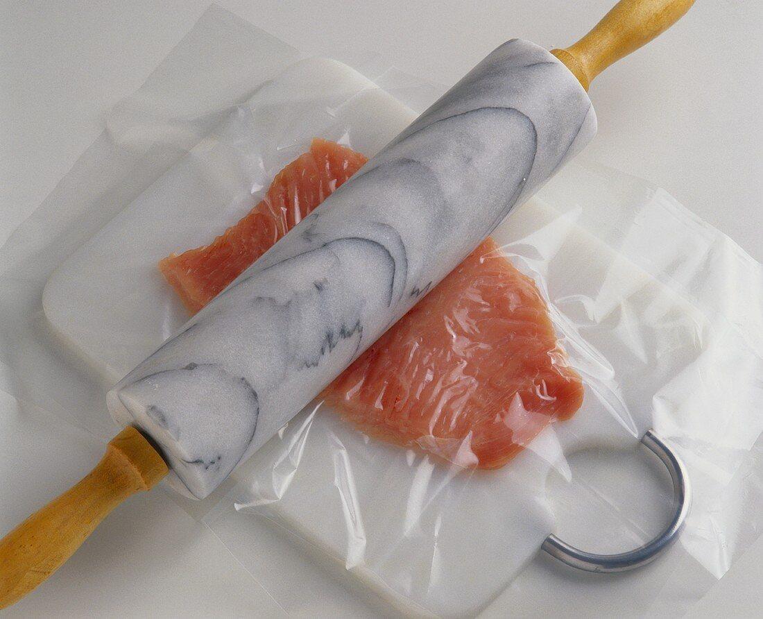 Flattening turkey meat between plastic foil with rolling pin