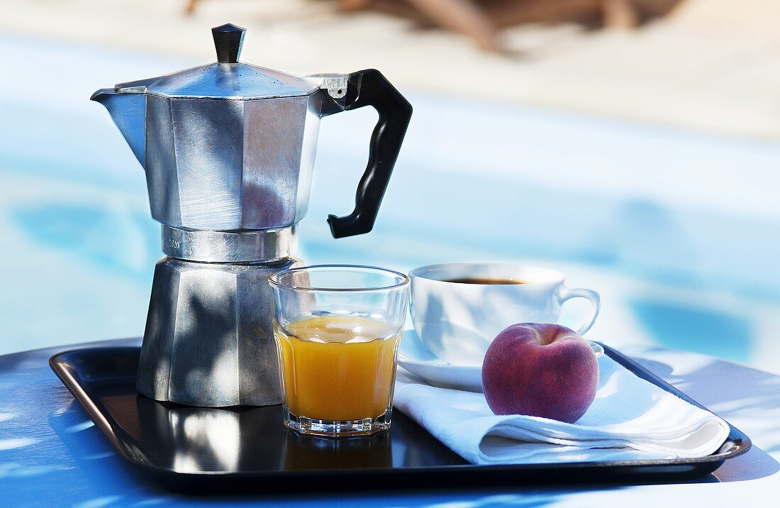 A breakfast tray by a swimming pool