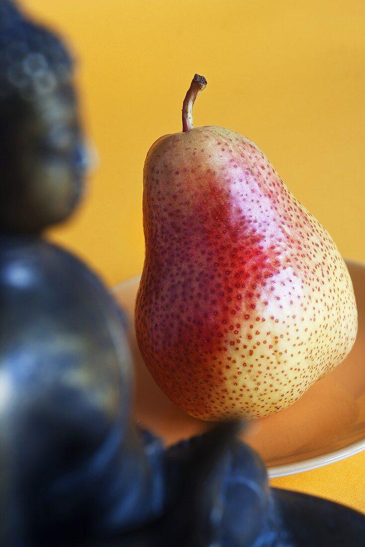 A pear and a Buddha statue