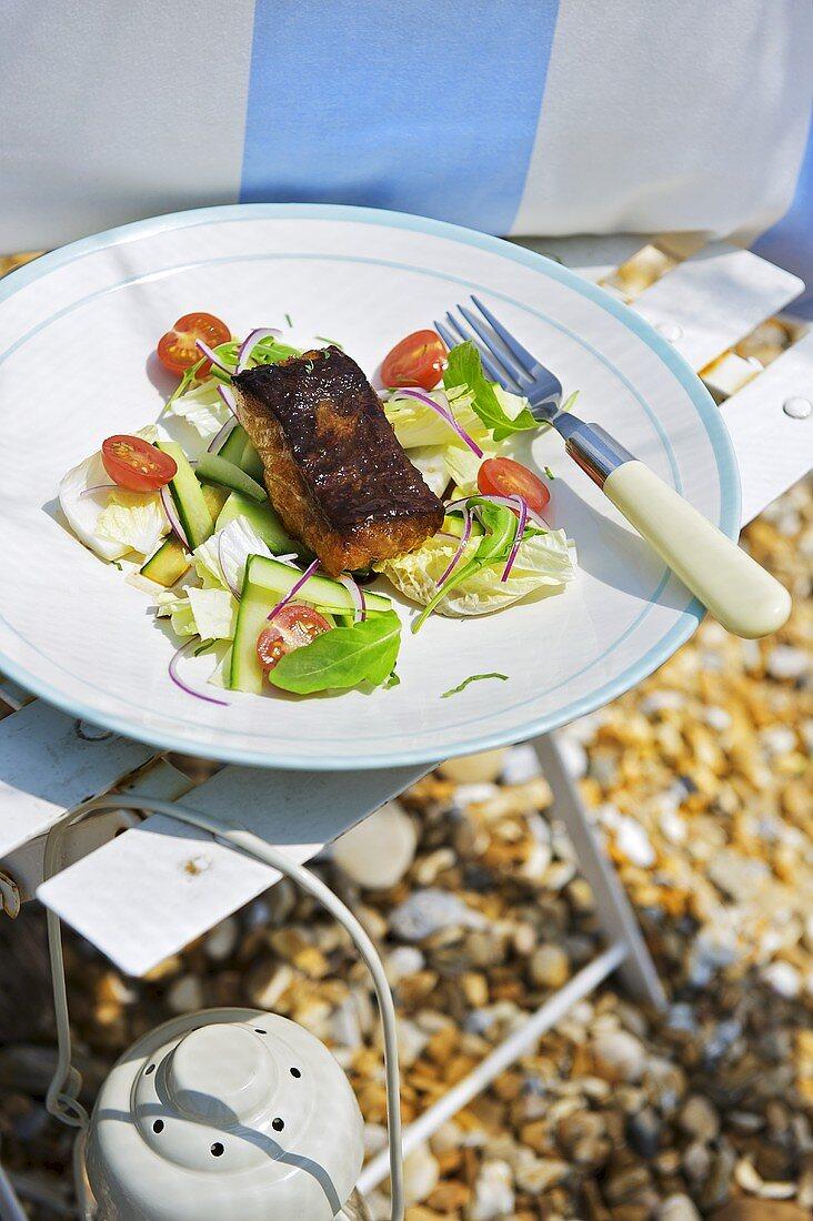 Gebratener Alaska-Seelachs mit Salat auf Teller am Strand